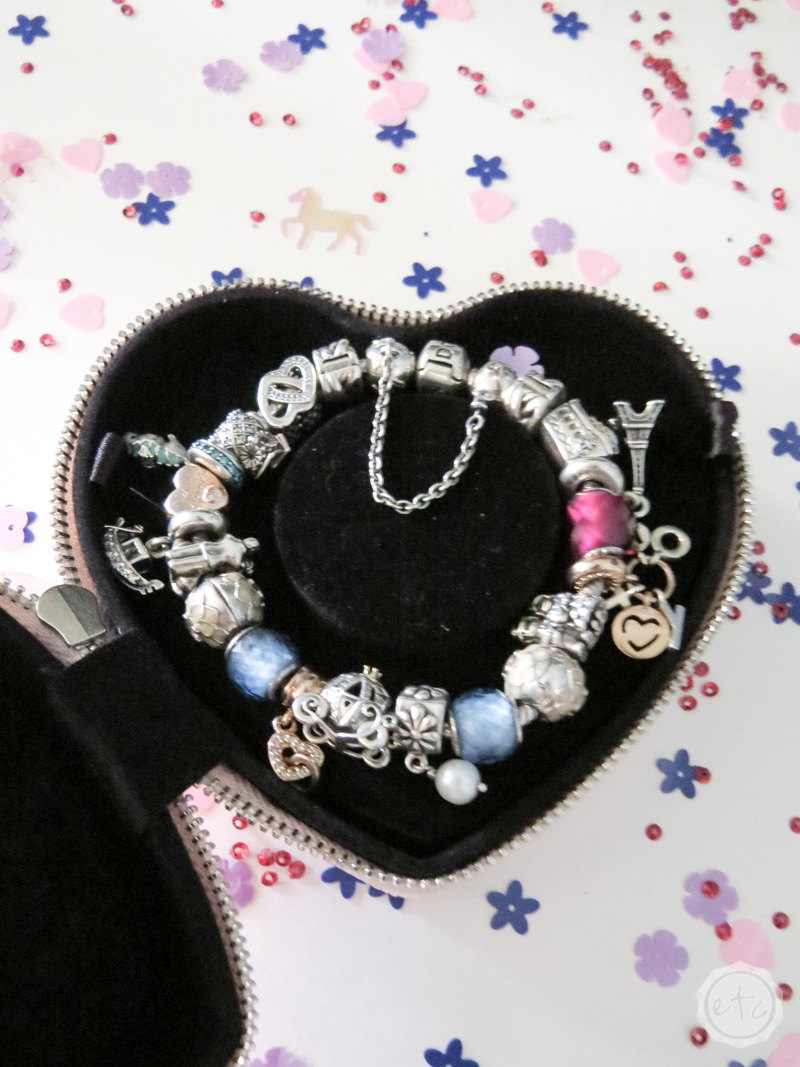 A pandora bracelet fully loaded with charms on a bed of anti-tarnish fabric inside it's case
