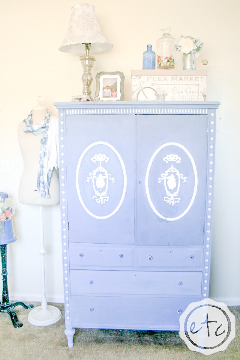 A large cabinet painted with blue and white furniture paint.