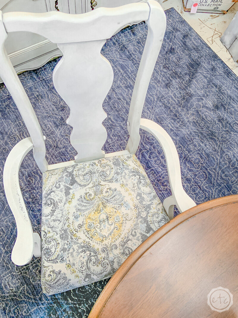 Gray and yellow damask fabric covering replacement dining chair seats.
