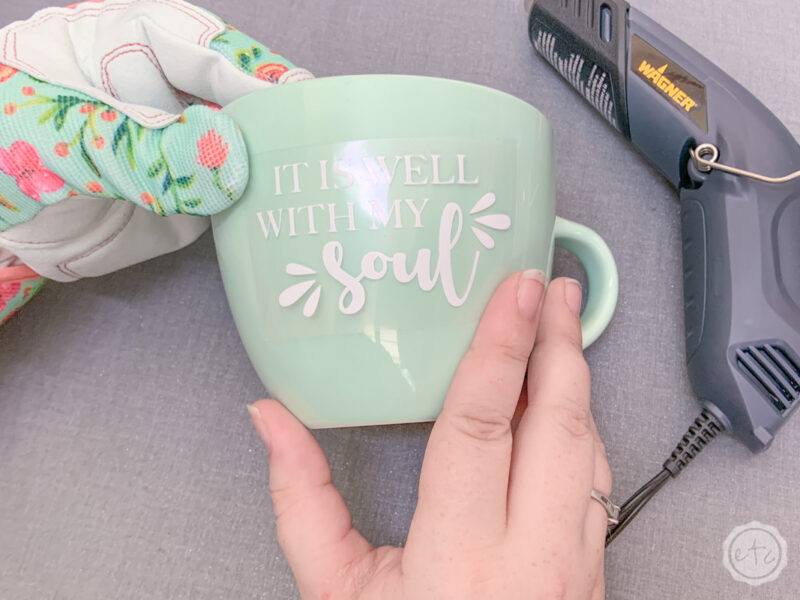 "Positioning a htv decal that reads ""it is well with my soul""  on a teal mug. Wearing floral teal and pink digz garden gloves and using a small wagner heat gun."